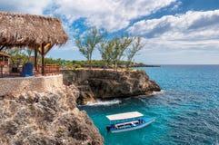 Plage rocheuse des Caraïbes avec l'eau de turquoise, le bateau de touristes et le phare dans Negril Jamaïque photo libre de droits