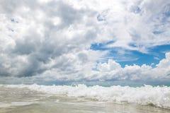 Plage sablonneuse avec l'eau claire et le beau ciel bleu avec des nuages Images stock