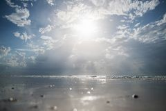 Plage sablonneuse avec l'eau claire et le beau ciel bleu avec des nuages Photos stock
