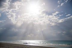 Plage sablonneuse avec l'eau claire et le beau ciel bleu avec des nuages Image stock