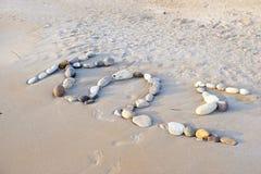 Plage sablonneuse avec une inscription d'île de Kos de pierres Image libre de droits