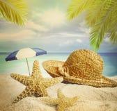 Plage sablonneuse, chapeau et étoiles de mer en sable d'été Images libres de droits