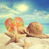 Plage sablonneuse, chapeau et étoiles de mer en été Image libre de droits