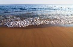 Plage sablonneuse et vague déferlante. Image stock