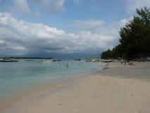 Plage sablonneuse tropicale avec de l'eau des bateaux, des arbres et bleu Photos libres de droits