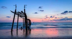 Plage scénique de coucher du soleil avec le pilier en bois abandonné Images stock