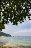 plage tropicale avec l'eau et les pierres claires réflexion et fond nuageux de ciel bleu Photos libres de droits