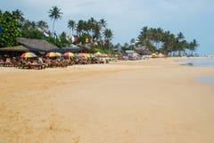 Plage tropicale avec les personnes, le café et le parapluie photographie stock