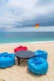 Plage tropicale avec les sacs à haricots et la table sur le sable Photo libre de droits
