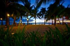 Plage tropicale dans le coucher du soleil Photo stock