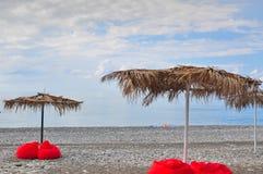 Plage tropicale dans le coucher du soleil avec les chaises et le parapluie de plage Photographie stock libre de droits