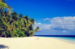 Plage tropicale de sable contre le ciel bleu Photos libres de droits