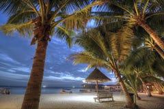 Plage tropicale et arbre d'ASEAN dans le coucher du soleil avec une hutte en bambou image libre de droits