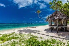 Plage vibrante tropicale sur l'île du Samoa avec le palmier et le fale Photographie stock