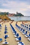 Plage vide avec les chaises longues bleues et l'eau de mer calme avec l'ol images libres de droits