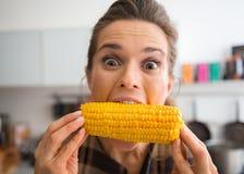 Plagend, gelukkige vrouw die grote beet van maïskolven nemen Stock Fotografie