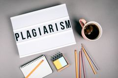 Plagiarism. Text in light box. Pink coffee mug on gray background stock photography