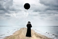 Plague doctor with black balloon in seaside.