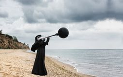 Plague doctor blows black balloon. Outdoor portrait with dramatic sky in background Stock Image