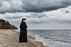 Plague doctor in seaside. Royalty Free Stock Photos