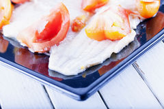 Plaice. With tomatoes over black reflecting plate, horizontal image Stock Photography