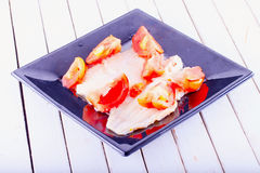 Plaice. With tomatoes over black reflecting plate, horizontal image Royalty Free Stock Photography