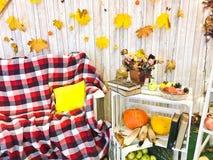 Plaid à carreaux sur un fauteuil et une table en bois avec des livres de vintage attachés avec la ficelle et un vase, herbier, po photo stock