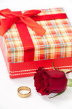 Plaid box with a red rose and golden ring Royalty Free Stock Photography