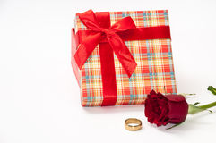 Plaid box with a red rose and golden ring Stock Photos