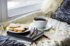 Plaid, cuscino, biscotti e tazza di caffè sul davanzale della finestra immagini stock