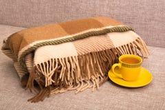 Plaid di lana a quadretti e tazza gialla con tè su un sofà Immagini Stock