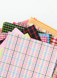 Plaid fabric. Pile of colorful checkered plaid fabric on white background with copy space Stock Photos