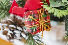 Plaid fabric wrapped holiday gift with gold twine, red ribbon an. D sprigs of pine and pine cone in background. Christmas giving, shopping and retail concept Royalty Free Stock Photography