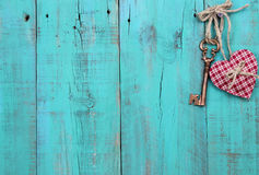 Plaid heart and bronze skeleton key hanging on antique teal blue wood door. Red checkered heart and skeleton key hanging by rope on vintage green wooden fence Royalty Free Stock Photography