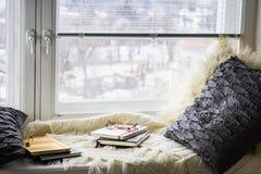 Plaid, oreillers, livres, journaux intimes sur la fenêtre photos libres de droits