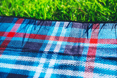 Plaid for picnic on green grass Royalty Free Stock Images