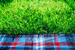 Plaid for picnic on green grass Stock Image