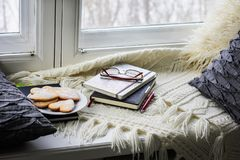 Plaid, pillows, books, cookies lie on the window. stock photo