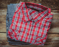 Plaid shirt and pair of jeans on wooden background. Vi Royalty Free Stock Photos