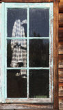 Plaid Shirt In Window. An old plaid work shirt hanging behind an old shed window with peeling and crackled turquoise paint Royalty Free Stock Photos