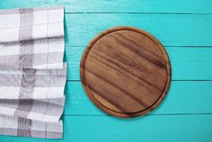 Plaid tablecloth, brown cutting board for pizza on blue wooden table. Wood background. Top view and mock up.Copy space royalty free stock images