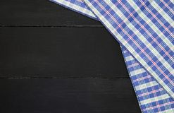 Tablecloth. The plaid tartan tablecloth on black wooden table in top view Royalty Free Stock Image