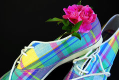 Plaid Tennis Shoes. Plaid canvas tennis shoes accented by a hot pink rose royalty free stock images