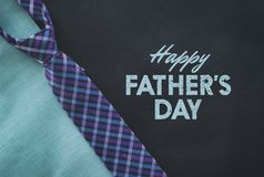 Plaid tie for fathers day. Blue and purple plaid tie for fathers day graphic against black and blue grunge background Royalty Free Stock Photos