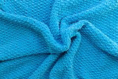 Plaid tricottato blu luminoso fatto del filato della peluche Materiale molle Struttura di lana Mestiere Handmade immagini stock