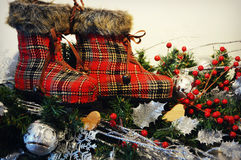 Plaid Winter Boots. A fun winter decoration of red plaid winter boots or stockings on top of evergreen branches with red berries, silver snowflakes and mistletoe Royalty Free Stock Image