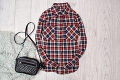 Plaiddamenhemd, schwarze Handtasche auf dem Webpelz Modernes Konzept, hölzerner Hintergrund, Draufsicht Stockbilder
