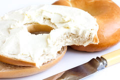 Plain bagel with knife, spread with cream cheese and bite missin Royalty Free Stock Images