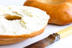 Plain bagel with knife, spread with cream cheese, detail. Stock Photo