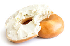 Plain bagel spread with cream cheese and bite missing. Isolated. Royalty Free Stock Images